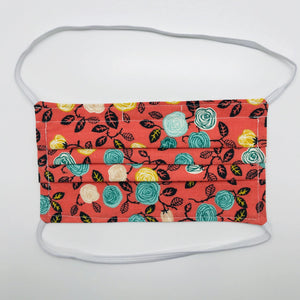 "Made with three layers of flowers on orange print 100% quilting cotton, this mask includes a filter pocket located in the pleats in the back of the mask for a filter of your choice, elastic head bands and a bendable aluminum nose. Machine wash and dry after each use. 7"" H x 7.5"" W"