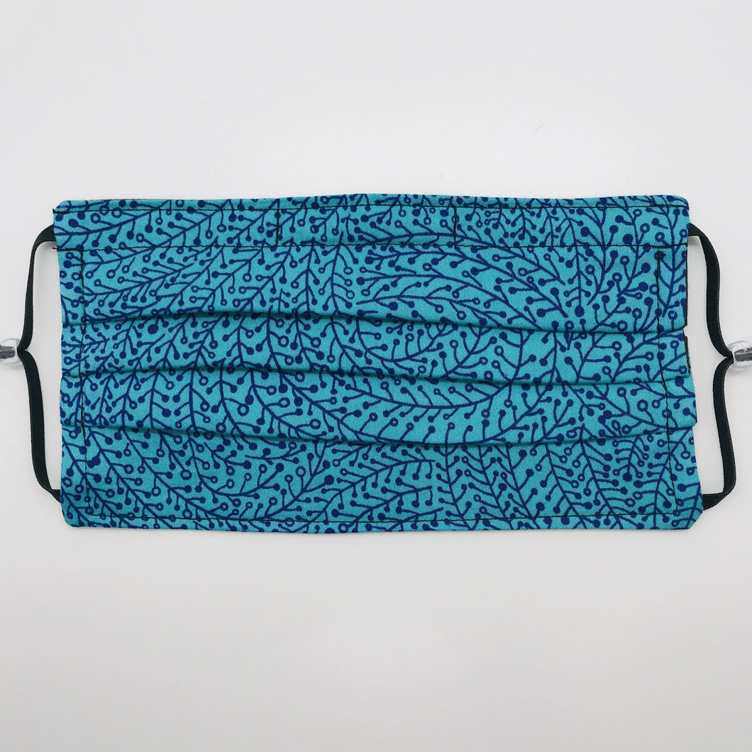 "Masks are made of 2 layers of 100% quilting-weight blue/teal swirl print cotton fabric. The mask has elastic adjustable ear loops and a bendable aluminum nose piece. Machine wash and dry after each use. 7"" H x 7.5"" W"