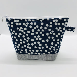 "The pouch is made from 100% quilting cotton with a white dots on blue print, Kaufman Essex cotton/linen for the base, and a layer of fleece. The cute metal tassel gives an added touch. 7.5 W x 6""H x 2.5""D. Machine washable and dryer safe, or air dry."
