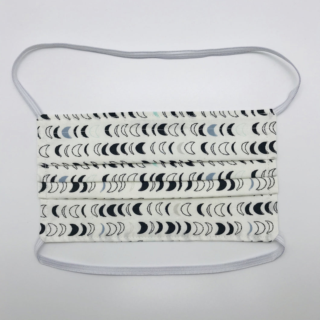 "Masks are made of 2 layers 100% quilting cotton featuring blue, white and black half moons in rows on white background print, over the head elastic loops and a bendable aluminum nose. Wash in washing machine and dry in dryer after each use. 7"" H x 7.5"" W"