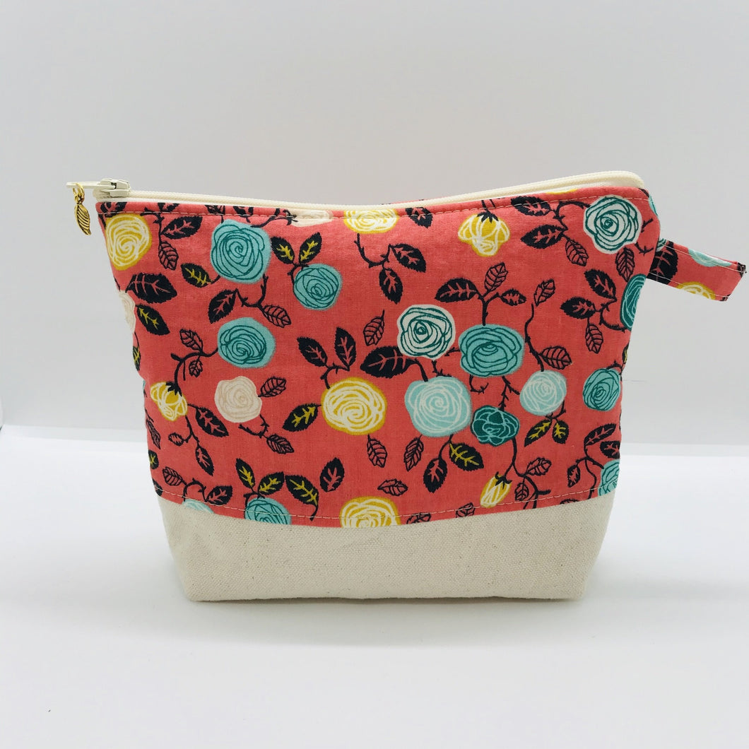 "The pouch is made from flowers on orange quilting cotton, an inner layer of fleece, essex/linen for the base and a cute metal tassel. The pouch design is from the Becca Bags pattern from Lazy Girl Design. Machine washable and dryable or air dry. 7.5W x 6""H x 2.5""D"