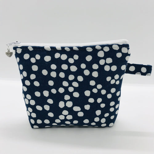 "The pouch is made of 100% quilting cotton of a white dots on blue print and a layer of fleece for stability. The cute metal tassel gives an added touch. 6""W x 4.5"" H x 1""D. Machine washable and dryer safe, or air dry."