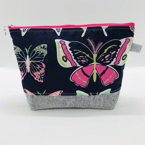 "The pouch is made from 100% quilting cotton with a large pink and white butterflies on blue print by Art Gallery Fabrics, Kaufman Essex cotton/linen for the base, and a layer of fleece. The cute metal tassel gives an added touch. 7.5 W x 6""H x 2.5""D. Machine washable and dryer safe, or air dry."