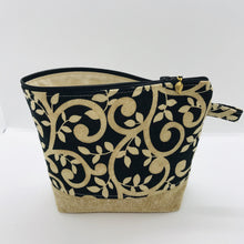 "Load image into Gallery viewer, The pouch is made from 100% quilting cotton with a gold swirls on black print, Kaufman Essex cotton/linen for the base, and a layer of fleece. The cute metal tassel gives an added touch. 7.5 W x 6""H x 2.5""D. Machine washable and dryer safe, or air dry."