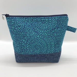 "The pouch is made from 100% quilting cotton with a blue/teal vine maze print, Kaufman Essex cotton/linen for the base, and a layer of fleece. The cute metal tassel gives an added touch. 7.5 W x 6""H x 2.5""D. Machine washable and dryer safe, or air dry."