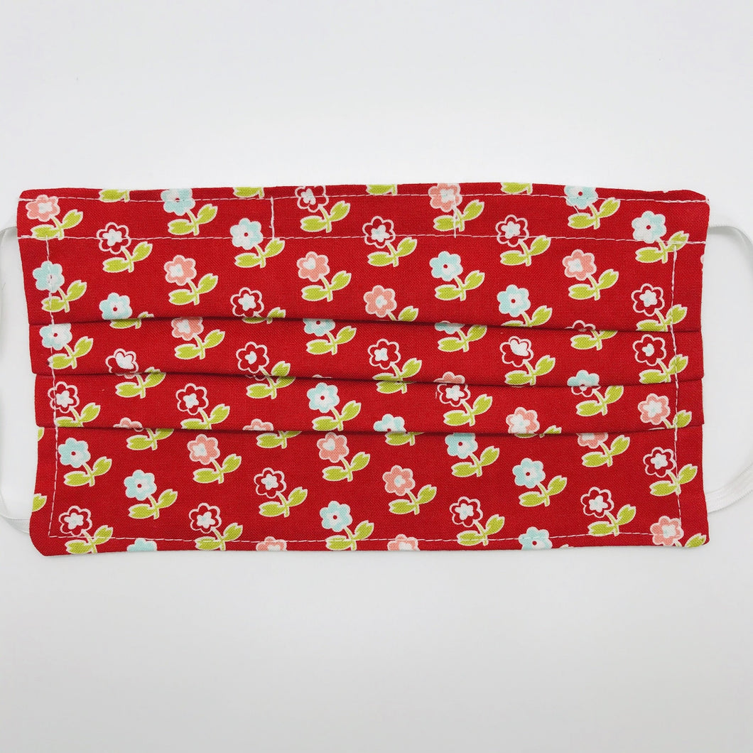 "Masks are made of 2 layers of 100% quilting-weight cotton fabric with a vintage picnic flowers on red print. The elastic adjustable ear loops tightened with a craft bead to make them comfortable to fit a wider range of sizes. The masks also have a bendable aluminum nose piece. Machine wash and dry after each use.     7"" H x 7.5"" W"