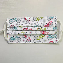 "Load image into Gallery viewer, 100% quilting-weight sport themed white back ground with blue, red and green bicycles print cotton face mask with adjustable elastic ear loops and bendable nose piece. Washable, reusable fabric face mask. Wash in washing machine and dry in dryer after each use. 7"" H x 7.5"" W  Fabric-  Sunday Ride White by Cherry Guidry of Contempo Studio for Benartex"
