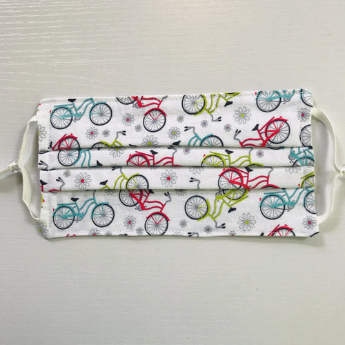 "100% quilting-weight sport themed white back ground with blue, red and green bicycles print cotton face mask with adjustable elastic ear loops and bendable nose piece. Washable, reusable fabric face mask. Wash in washing machine and dry in dryer after each use. 7"" H x 7.5"" W  Fabric-  Sunday Ride White by Cherry Guidry of Contempo Studio for Benartex"