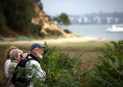An older gentleman and two older women using binoculars to bird watch by the sea