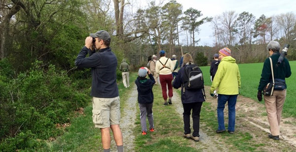 people on trail using binoculars