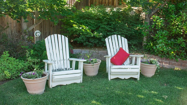 white chairs in grassy backyard