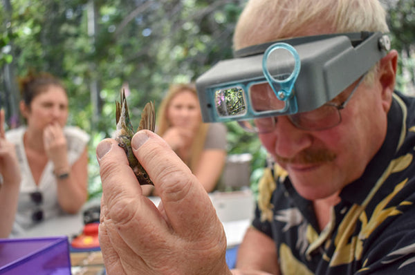 man holding hummingbird with glasses