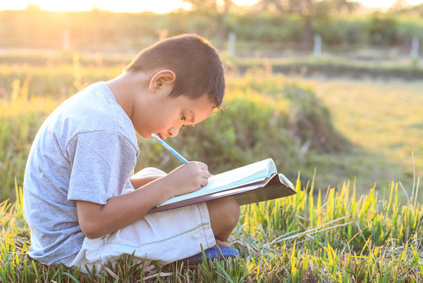 Young boy outside writing in notebook