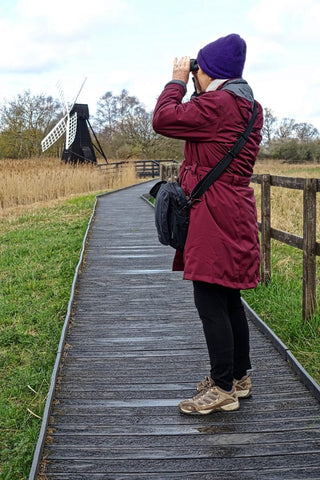 A middle aged woman birding with binoculars on a wooden path, in the middle of a meadow.