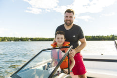 Dad letting his son help steer the boat