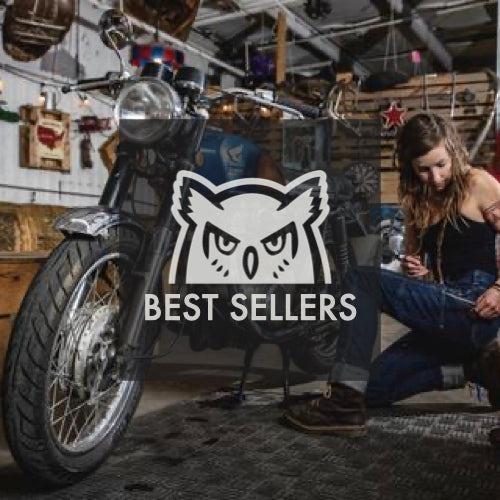 Woman repairing motorcycle, wearing Dovetail Maven Slim indigo denim pant and work boots.