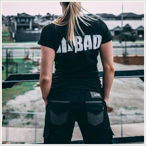 Lifestyle image of a woman wearing a BAD black tee and BAD 925 work pants in black. The picture is taken from behind and she is looking out over a construction site.
