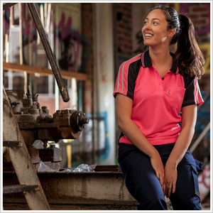 Lifestyle image of a woman wearing a BAD Hit-vis Pink Polo and BAD 925 Work Pants in Navy. She is sitting on a steel beam at a construction site.