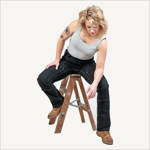 Woman wearing Dovetail Britt Utility pants in No Fade Black Canvas. She is straddling a small step latter. She is also wearing a grey tank top and brown work boots.