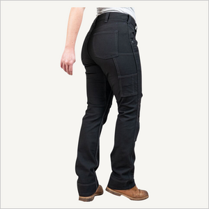 Back angled view of woman wearing Dovetail Brit Utility pants in No Fade Black Canvas.