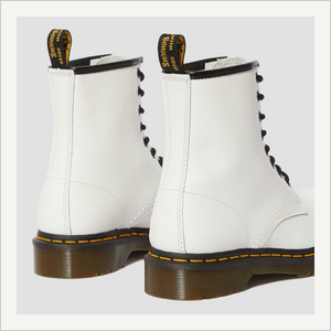 Back angled view of a pair of Dr. Martens 8 Eye 1460 Slip Resistant Lace Boots in White.