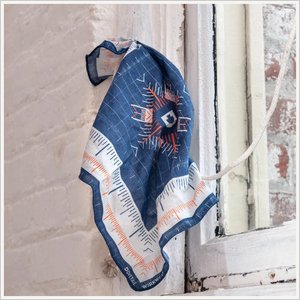 Lifestyle image of Dovetail Women's Baesline Bandana hanging on a whitewashed brick wall in front of a window.