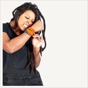 Lifestyle image of a woman with dreads wearing black overalls and a Dovetail Baseline Bandana in paprika and blue on her wrist. She is biting one end of the bandana to tie it onto her wrist.
