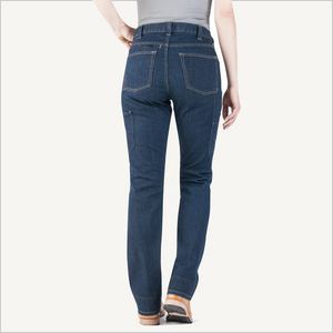 Backside view of woman wearing Dovetail Woman's Britt Utility Pant in Reinforced Indigo Denim.  She is wearing a grey shirt and visible from the waist down.