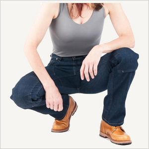 Woman squatting down wearing Dovetail Woman's Britt Utility Pant in Reinforced Indigo Denim.  She is wearing a grey tank top and camel work boots and is visible from the neck down.