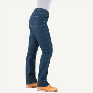 Side view of woman wearing Dovetail Woman's Britt Utility Pant in Reinforced Indigo Denim.  She is wearing a grey shirt and camel work boots and is visible from the waist down.