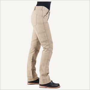 Side view of woman wearing Dovetail Women's Britt Utility Pant in Natural Stretch Canvas. She is wearing a black shirt and black work boots and is only visible from the waist down.