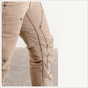 Close up of a woman wearing Dovetail Women's Britt Utility Pant in Natural Stretch Canvas. Her left leg is visible from the top to her calf. And the upper half of her right thigh is visible.