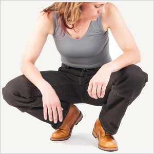 Woman squatting down wearing Dovetail Woman's Day Construct Stretch Canvas Work Pant in Dark Brown. She is wearing a grey tank top and camel work boots and is visible from the neck down.