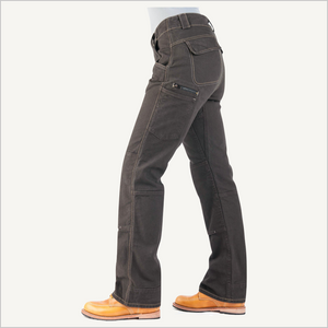 Side view of woman wearing Dovetail Day Construct Stretch Canvas Work Pant in Dark Brown. She is wearing a grey shirt and camel work boots and is visible from the waist down.