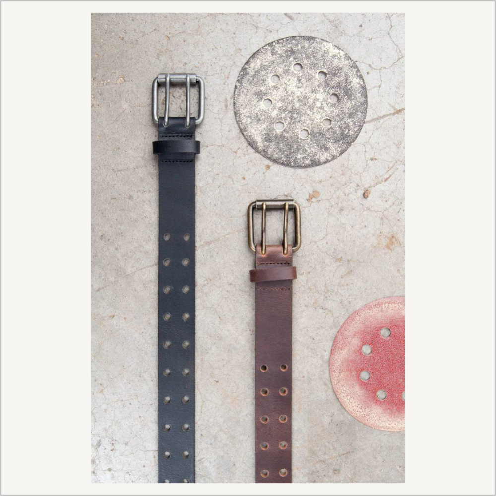 Lifestyle image of Dovetail Women's Double Pronged Work Belts in Black and Dark Brown. The belts are laid vertically side-by-side on a marble surface with sanding discs above and to the right.