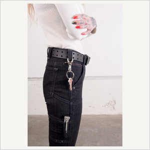 Lifestyle image of woman wearing Dovetail Women's Double Pronged Work Belt in Black. The view is from the side. She is wearing a white thermal long sleeve shirt and Dovetail Maven Slim in Black Stretch Denim. She has keys hanging from a belt loop and a tool in a lower pocket. Her nails are painted red and black and she has tattoos on her hand.