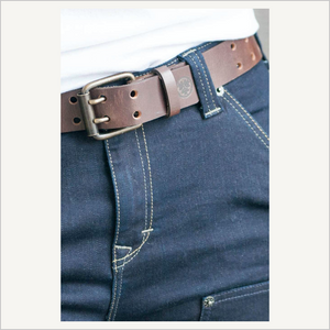 Close up of front of woman wearing Dovetail Double Pronged Work Belt in Dark Brown. She is wearing a white tee shirt and blue work jeans. Only half of her waist is visible.