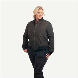 Woman wearing Dovetail Evaleen Waxed Canvas Trucker Jacket in Olive. She is facing the camera and her body is visible to her knee. She is wearing dark grey work pants.
