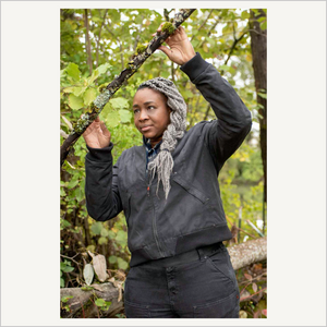 Lifestyle image of Dovetail Evaleen Waxed Canvas Trucker Jacket in Dark Grey. A woman is wearing the jacket and standing in the woods. There are green trees behind her and she is holding onto a branch over her head.