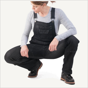 Woman wearing Dovetail Freshly Overall in Black Stretch Denim. She is facing the camera and squatting down and has on black work boots and a grey long sleeve shirt. Most of her body is visible and she is looking to the side.