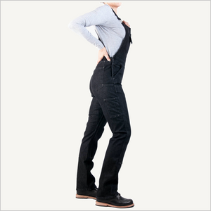 Woman wearing Dovetail Freshly Overall in Black Stretch Denim. Her side is facing the camera and she's has on black work boots and a grey long sleeve shirt. Only her body is visible.