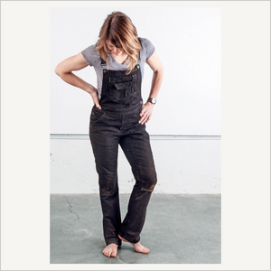 Woman wearing Dovetail Freshly Overall in Black Stretch Denim. She is facing the camera and looking down. She is barefoot and has a grey short sleeve tee on.
