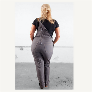 Woman wearing Dovetail Freshley Overall in Grey Stretch Canvas. She is facing away from the camera and has one strap unhooked. She is wearing a black tee.