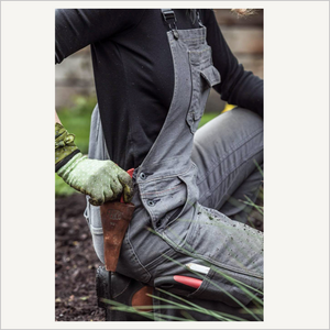 Lifestyle image of a woman wearing Dovetail Freshley Overall in Grey Stretch Canvas. She is kneeling in dirt and has several garden tools stored in her overalls. She has garden gloves and a black long sleeve shirt on.