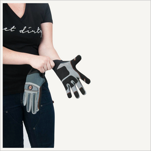 Woman wearing Dovetail Impact Protective Work Glove. She is putting one glove on her hand and holding the other glove. She is wearing a black tee and jeans and is only visible from her neck to her knee.