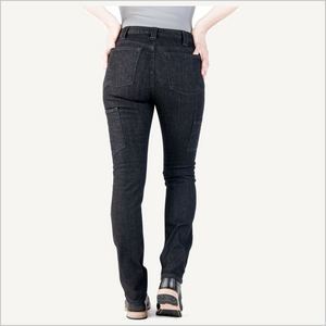 Backside view of woman wearing Dovetail Maven Slim Work Pant in Black Stretch Denim. She is wearing a grey shirt and black work boots and is visible from the waist down. Her hands are on her hips.