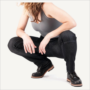 Woman squatting down, wearing Dovetail Maven Slim Work Pants in Black Stretch Denim. She is also wearing a grey tank top and black work boots.