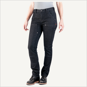 Woman wearing Dovetail Maven Slim Work Pants in Black Stretch Denim. She is facing the camera and visible from the waist down. She is wearing a grey shirt and black work boots.