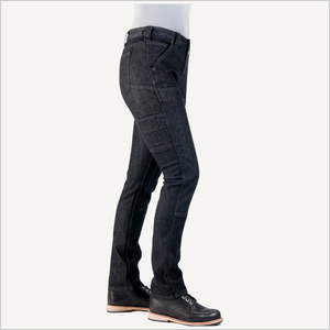 Woman wearing Dovetail Maven Slim Work Pants in Black Stretch Denim. Her side is facing the camera and visible from the waist down. She is wearing a grey shirt and black work boots.
