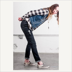Lifestyle image of woman wearing Dovetail Maven Slim Work Pants in Black Stretch Denim. She is also wearing a black and white plaid shirt and blue denim vest and checkerboard slip-on shoes. She is bending forward at the waist with her side visible to the camera. She is looking at the camera over her shoulder, with her hand clasped behind her back.